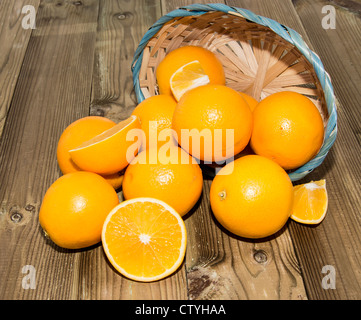 Oranges in a basket on wooden background - Stock Photo