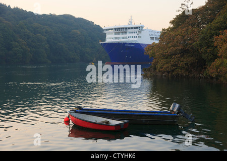 Small boats moored and large cargo ship laid up in deep Fal River during global recession. Falmouth, Cornwall, England, - Stock Photo