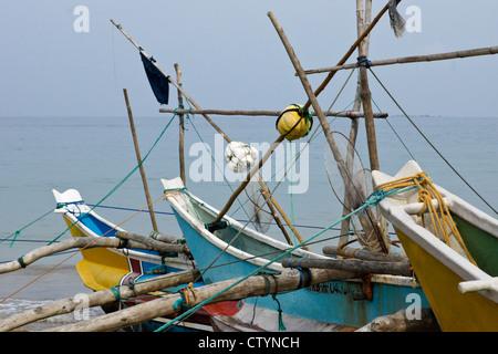 Outrigger fishing boats (oru or sea canoes) on beach, Kumarakanda, Sri Lanka - Stock Photo