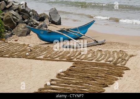 Outrigger fishing boat (oru or sea canoe) and net (madela) on beach, south coast of Sri Lanka - Stock Photo
