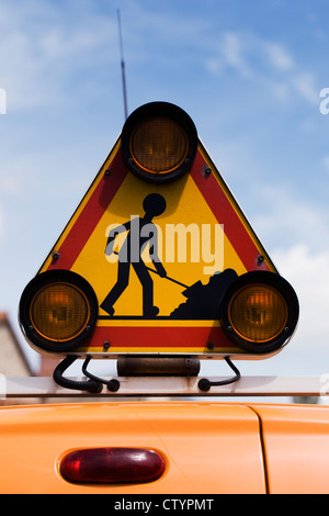 French roadworks sign on top of a van. - Stock Photo