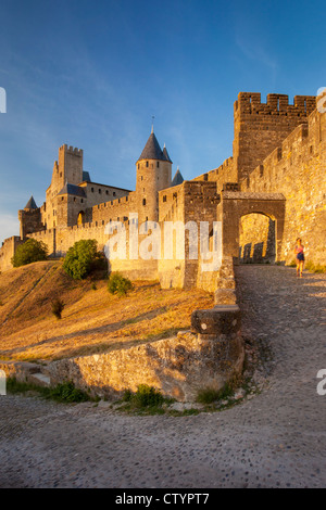 Lone female walks down the ramp from the entry gate to Carcassonne, Languedoc-Roussillon, France - Stock Photo