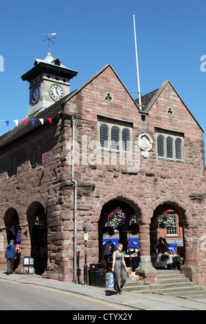 Woman carrying bag walking past the Market House in Ross on Wye, England, UK - Stock Photo