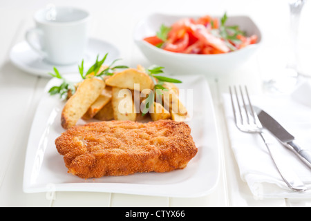Schnitzel with wedges and tomato salad - Stock Photo