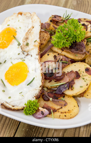 Fried Egg on a heap of roasted Potatoes on wooden background - Stock Photo