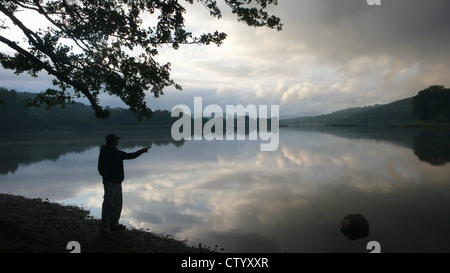 Man looking out over still lake - Stock Photo