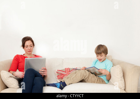 Mother and son relaxing on couch - Stock Photo