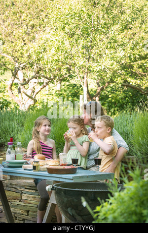 Family eating together at table outdoors - Stock Photo