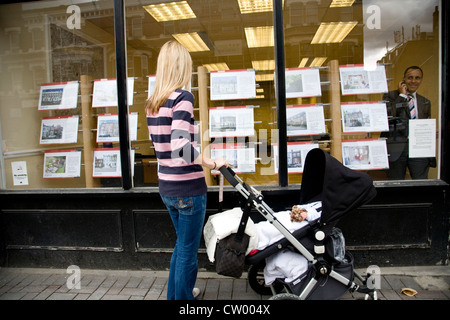 Woman and child look at properties advertised for sale in an Estate Agents window, London, UK. Photo:Jeff Gilbert - Stock Photo