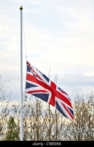 A union jack flag flies at half mast during a repatriation ceremony for four servicemen killed in action - Stock Photo