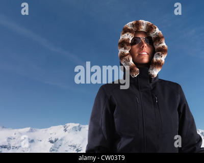 Woman wearing parka in snow - Stock Photo