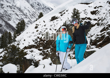 Skiers standing on snowy slope - Stock Photo