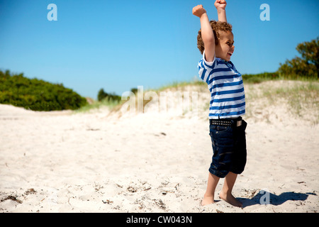 Young boy with arms stretched looks happy as he plays on the sand - Stock Photo