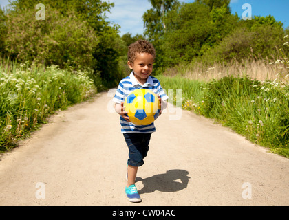 Little kid playing with a ball outdoors on a hot day - Stock Photo