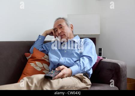 Older man watching television - Stock Photo