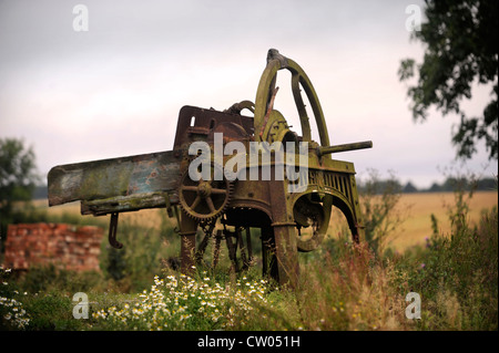 Vintage farm machinery on the site of a barn conversion in progress Warwickshire, UK - Stock Photo