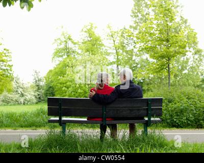 Older couple sitting on park bench - Stock Photo