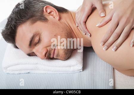 Smiling man having back massage - Stock Photo