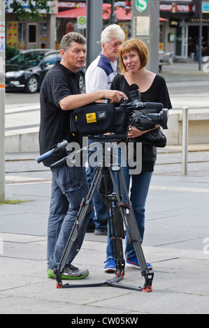 Television camera crew cameraman and female reporter with red hair, digital TV camera on professional tripod - Stock Photo