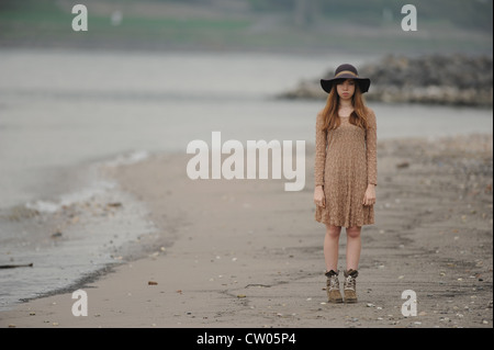 Teenage girl standing on sandy beach - Stock Photo