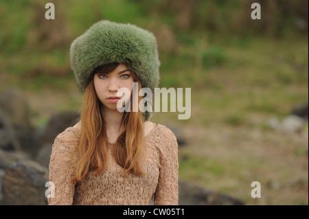 Teenage girl wearing fur hat outdoors - Stock Photo