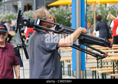 Caucasian male camera crew member carries a professional TV camera tripod on his shoulder - Stock Photo