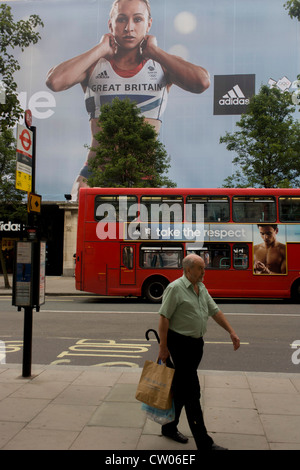 A man walks near the inspiring image of Team GB gold medallist heptathlete Jessica Ennis and diver Tom Daley which - Stock Photo