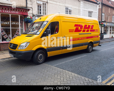 A yellow DHL parcels delivery van parked in Kirkgate Thirsk North Yorkshire - Stock Photo