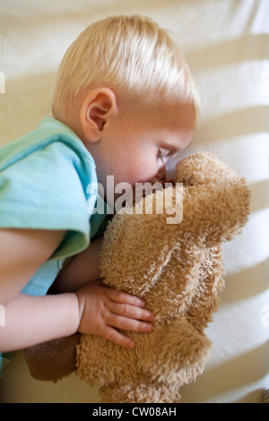 20 month old baby boy asleep whilst holding cuddly toy in cot - Stock Photo