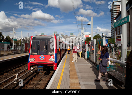 Passengers and a train at the DLR (Docklands Light Railway) station at Royal Victoria, London UK - Stock Photo