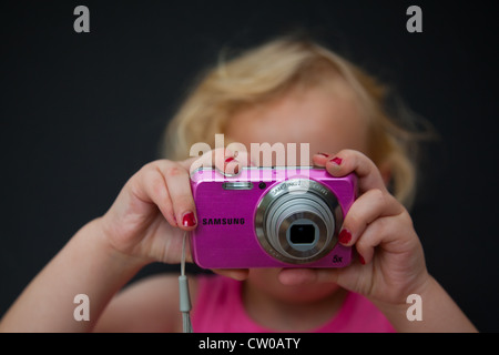 young girl with pink camera - Stock Photo