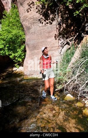 USA Utah, woman hiking in Kanarra Creek slot canyon near Zion National Park. - Stock Photo