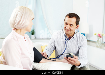 Portrait of mature man measuring blood pressure of his wife and looking at her - Stock Photo