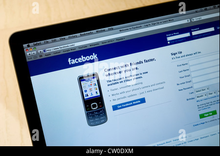 Laptop screen showing homepage view of facebook - popular social media - Stock Photo