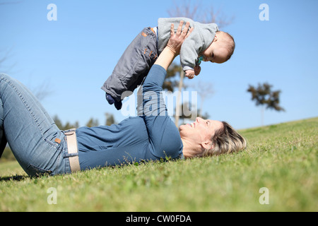 Woman playing with baby in grass - Stock Photo