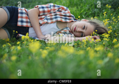 Woman laying in field of flowers - Stock Photo