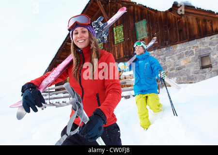 Skiers carrying skis and poles in snow - Stock Photo
