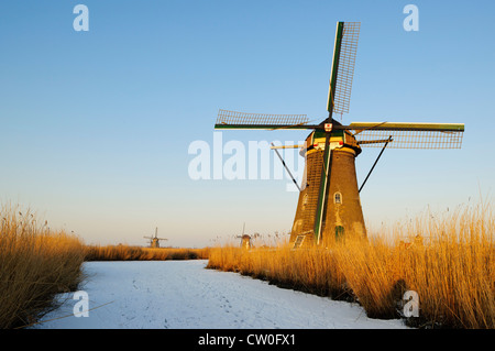 Windmill by river in rural landscape - Stock Photo