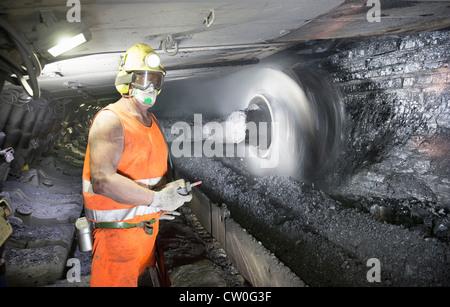 Coal miner working in mine - Stock Photo