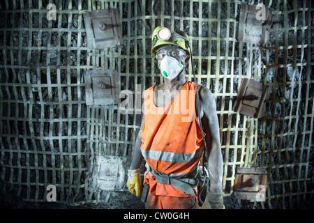 Coal miner standing in mine - Stock Photo