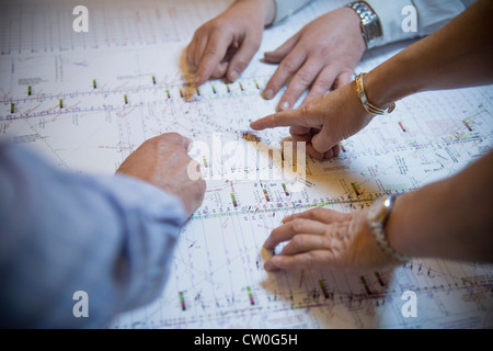 Business people reading coal mine plans - Stock Photo