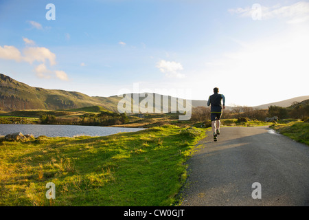 Man running on rural road - Stock Photo