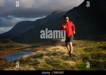 Hiker running on grassy hillside - Stock Photo