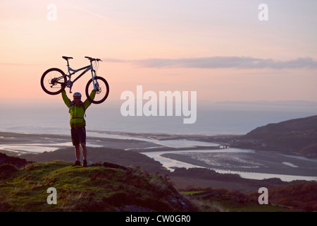 Man holding bicycle on hilltop - Stock Photo