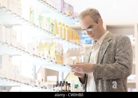 Man shopping in pharmacy - Stock Photo