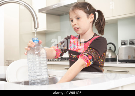 Girl filling up water bottle in kitchen - Stock Photo