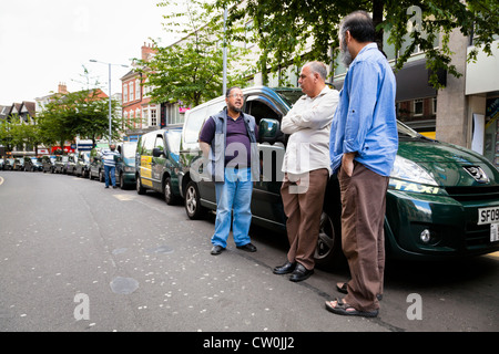 Taxi drivers standing by their cabs waiting for fares at a taxi rank in Nottingham city centre, England, UK - Stock Photo