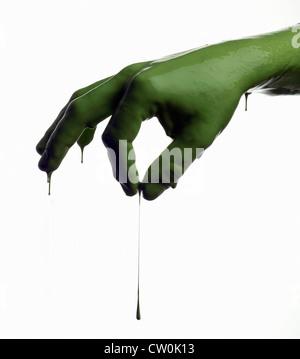 Green painted hand pinching - Stock Photo