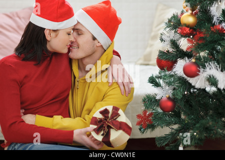 Romantic young couple with gift kissing near Christmas tree - Stock Photo