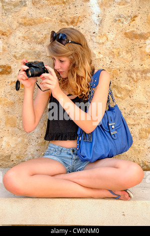 Pretty teenage girl, sitting cross legged, taking a photo in front of a stone wall. Airvault, Deux-Sèvres department, - Stock Photo